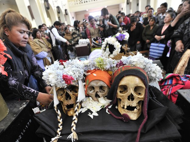"""Believers attend a mass in a chapel with their """"natitas"""" (flat-nosed) human skulls, at the cemetery in La Paz on Friday."""