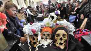 "Believers attend a mass in a chapel with their ""natitas"" (flat-nosed) human skulls, at the cemetery in La Paz on Friday."