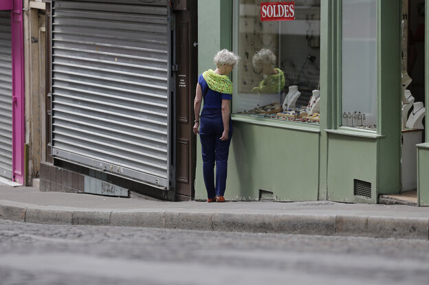 A woman walks amid both open and closed shops during a Sunday morning stroll at the Butte Montmartre in Paris, in July. Under France's Byzantine rules on Sunday trading, shops at the top of the hill are in a designated tourist area and so can open, but those at the bottom cannot.