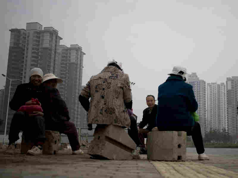 Migrant workers rest during their lunch break near newly built residential apartment buildings in Xi'an, in central China's Shaanxi province, on Nov. 6.