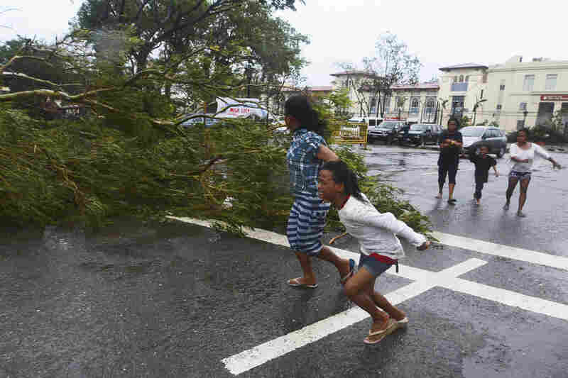 Residents rush to safety past a fallen tree as strong winds from the typhoon hit Cebu City.