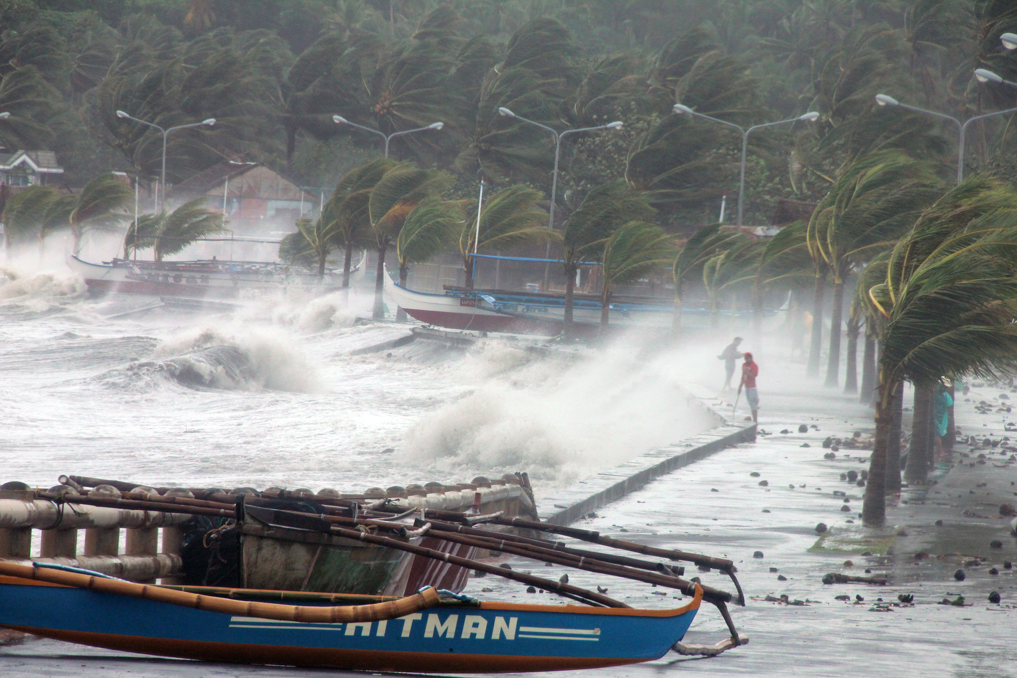 Legazpi City residents stand along a sea wall, as high waves and strong winds hit.