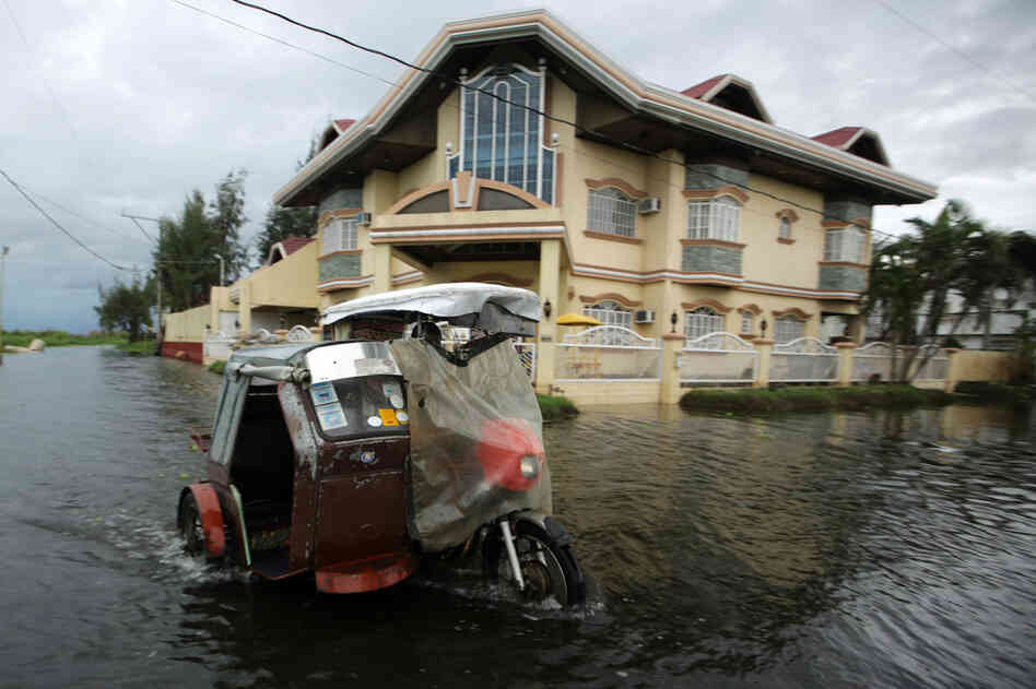 A three-wheel motorcycle maneuvers in floodwaters in Taguig City. Haiyan, the most powerful cyclone in decades, has killed at least four people, according to The Associated Pr