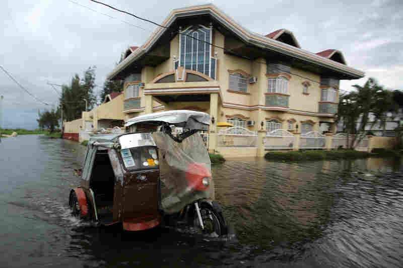 A three-wheel motorcycle maneuvers in floodwaters in Taguig City. Haiyan, the most powerful cyclone in decades, has killed at least four people, according to The Associated Press.