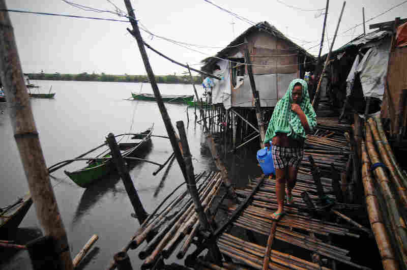 A woman walks in a fishing village in Bacoor. The good news is that Haiyan is now back out over water, a sign that the worst is over.