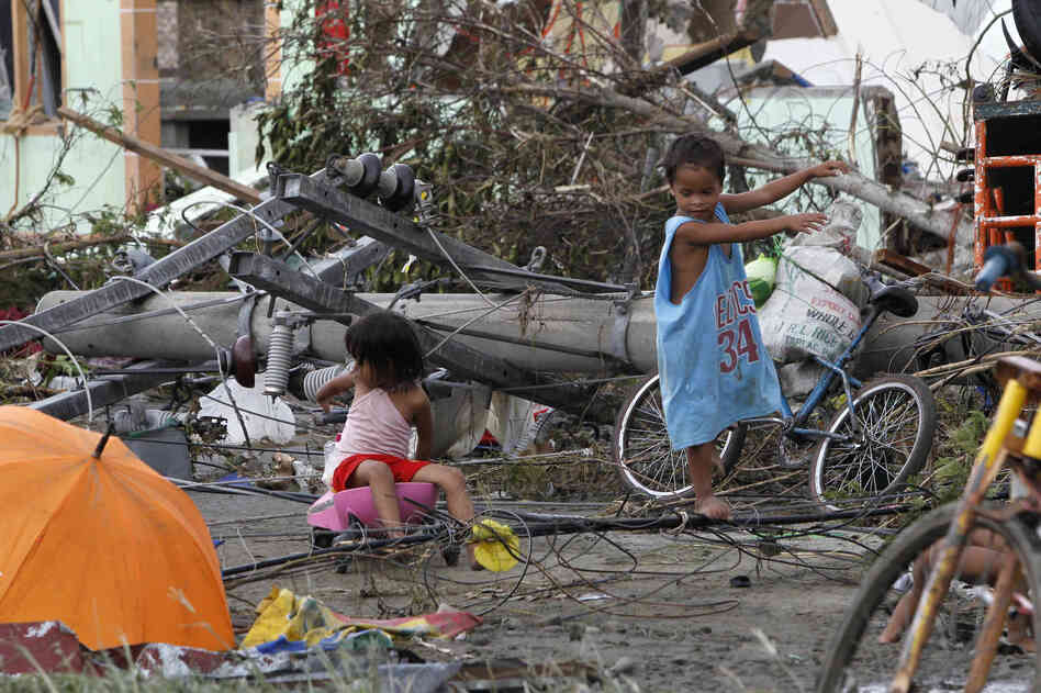 Children play near electric posts which were damaged after super Typhoon Haiyan battered Tacloban city in the central Philippines.