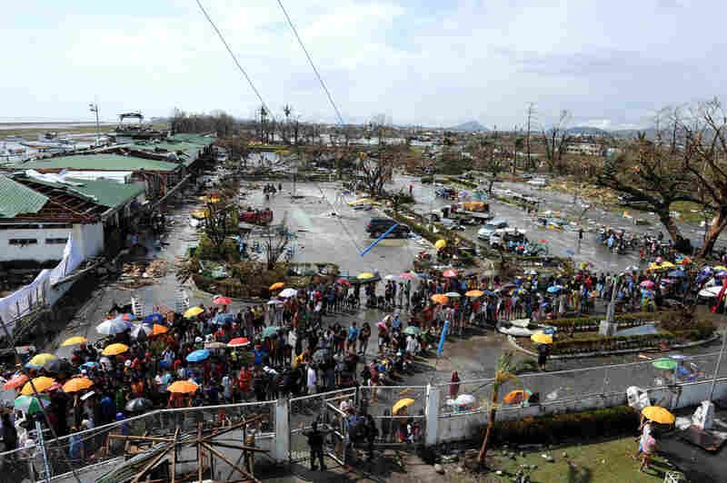 Typhoon survivors line up to receive relief goods being distributed at the Tacloban airport Sunday.