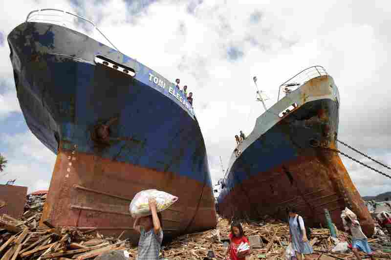 Survivors pass by two large boats Sunday after they were washed ashore by strong waves caused by Typhoon Haiyan in Tacloban city.