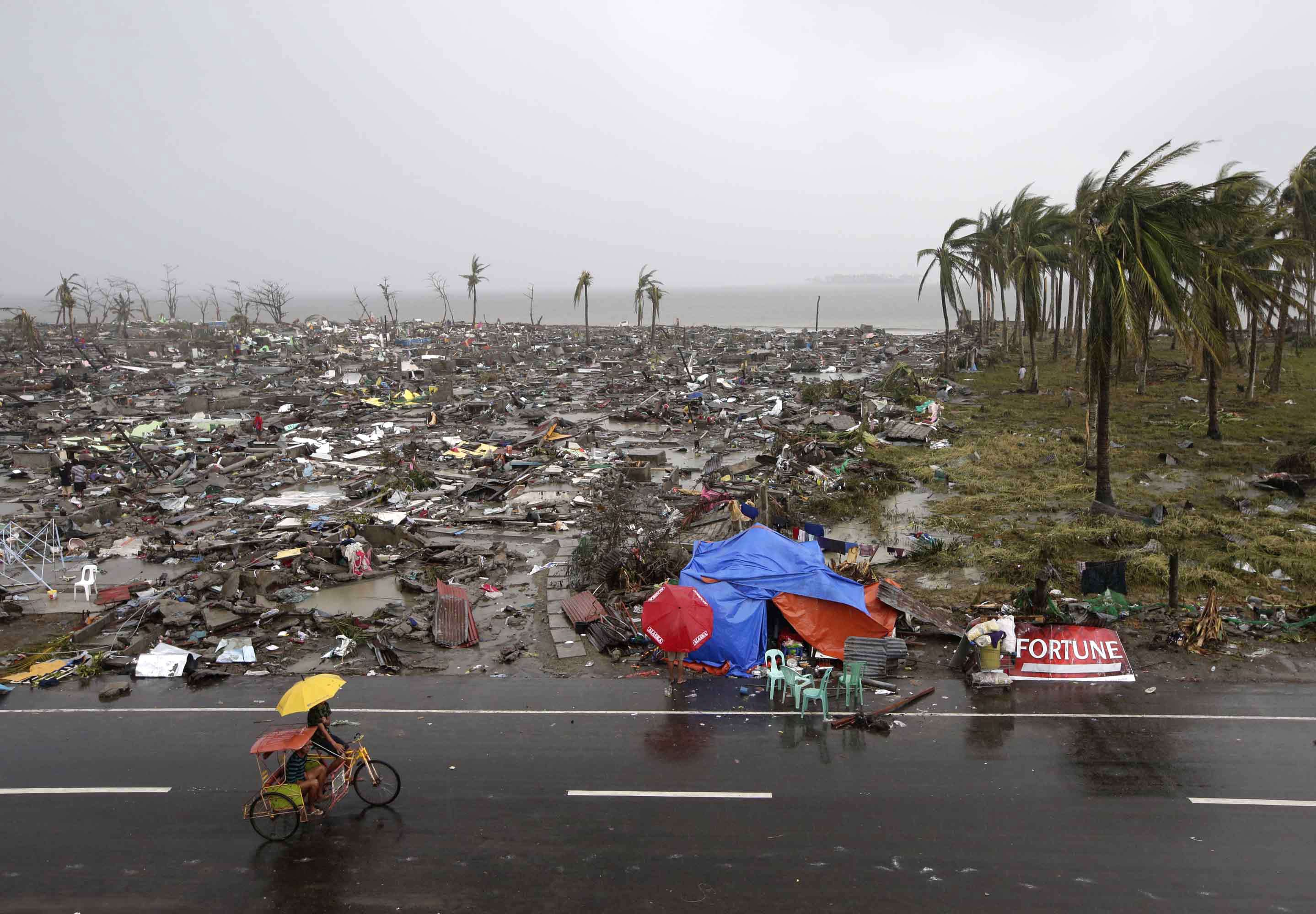 Residents walk past the devastation caused by Typhoon Haiyan.