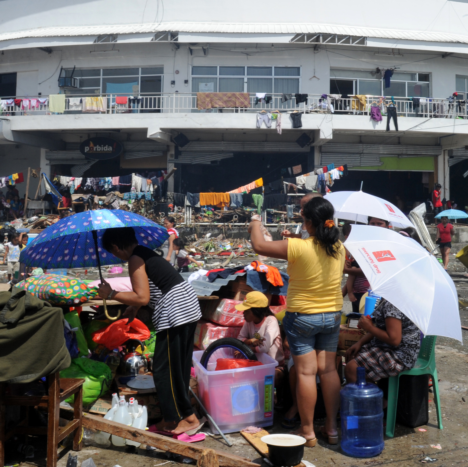 Residents rest outside a stadium used as an evacuation center in Tacloban, Leyte province, central Philippines on Sunday after devastating Typhoon Haiyan hit the city on Friday.