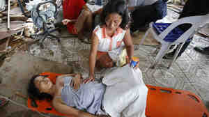 A woman comforts a pregnant relative suffering labor pains at a makeshift birthing