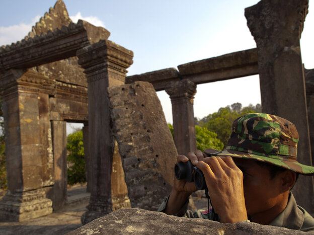 A Cambodian soldier looks across at the Thai border from