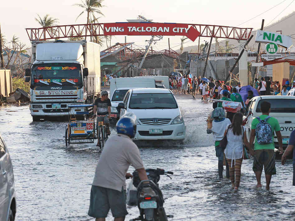 Residents wade through flood waters on Sunday in Tacloban City, Leyte, Philippines, in the aftermath of Typhoo
