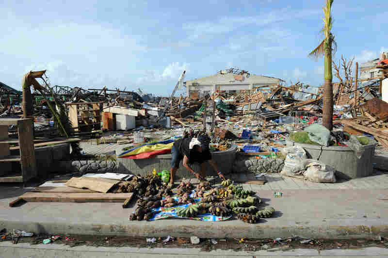 An elderly resident sells root crops and fruit next to the destroyed public market in the town of Guiuan in the Philippines.