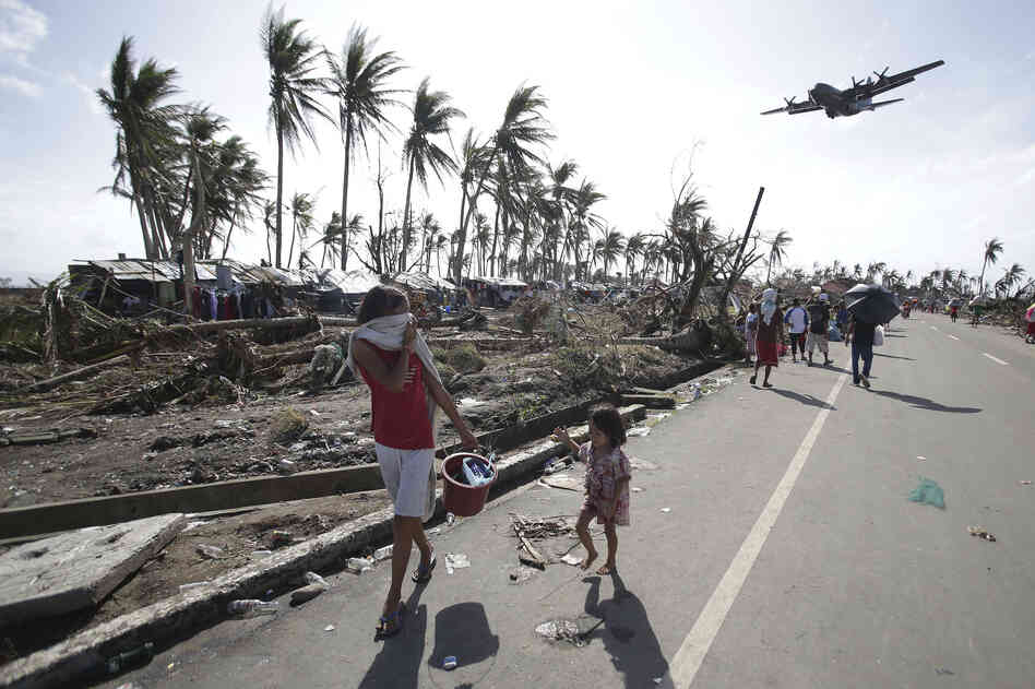 "A military plane arrives in typhoon ravaged Tacloban city. Phillipine President Benigno Aquino has declared ""a state of national calamity."""