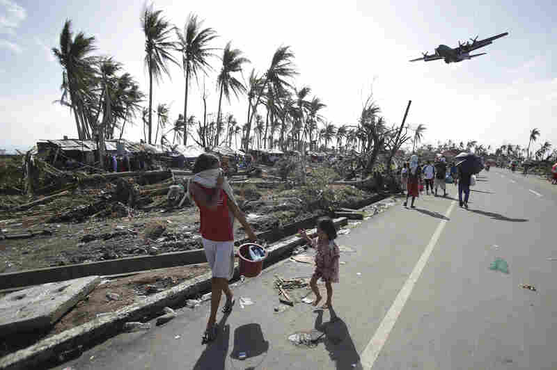 """A military plane arrives in typhoon ravaged Tacloban city. Phillipine President Benigno Aquino has declared """"a state of national calamity."""""""