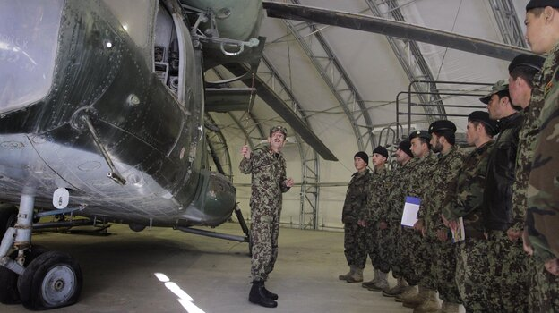Afghan trainer Col. Din Mohammad, standing in front of a Soviet-made helicopter, speaks to new group of Afghan pilots and air crews at the Air Force University