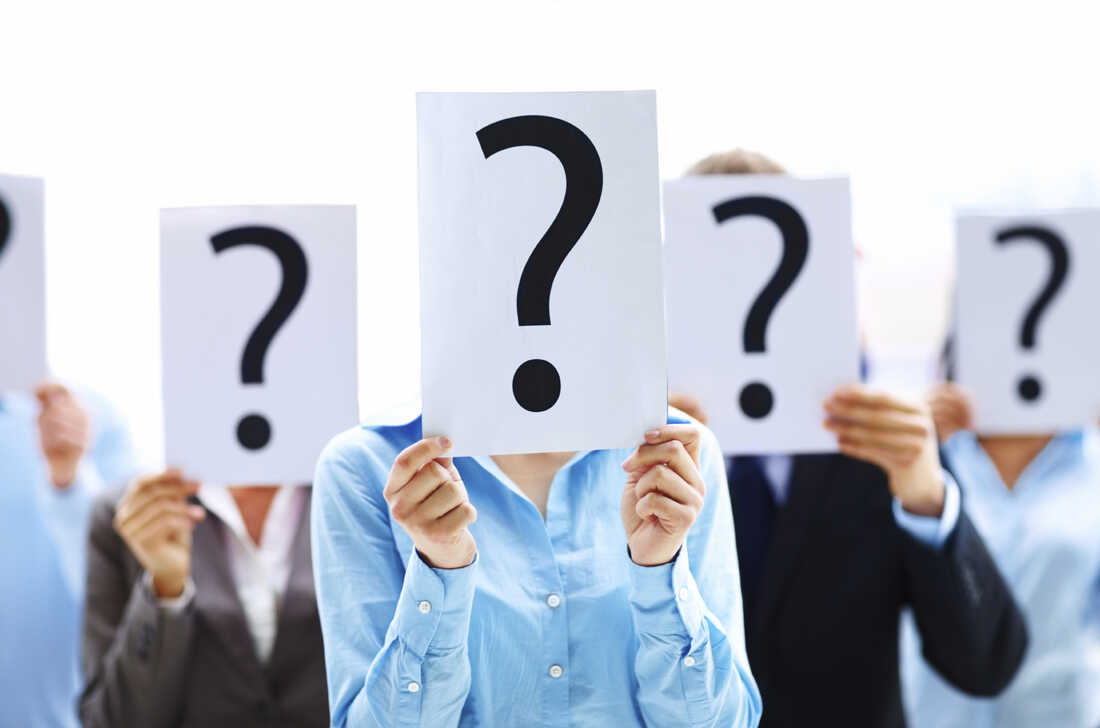 A group of people holding up question marks in front of their faces.