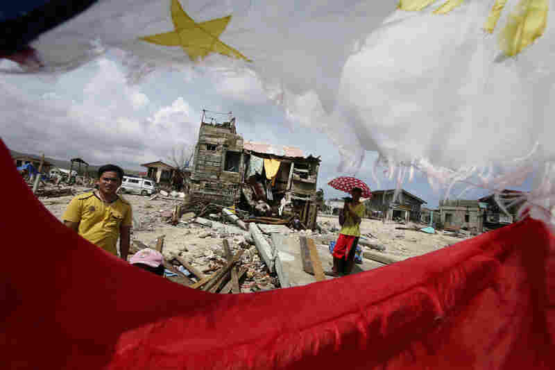 Residents, waiting for relief supplies, are framed by a tattered Philippine flag in Hernani. Typhoon Haiyan was one of the most powerful typhoons ever recorded.