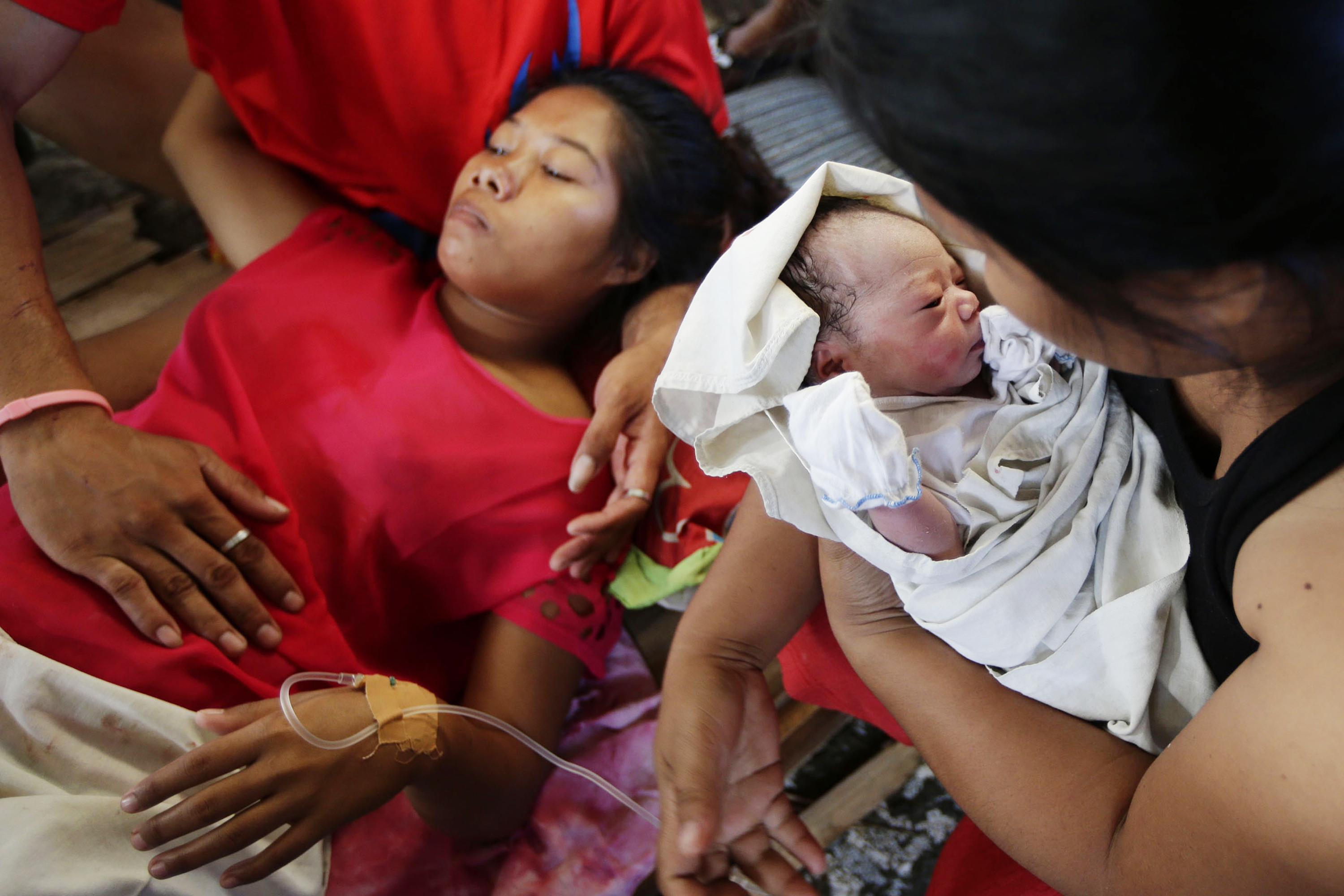 New-born baby Bea Joy is held as mother Emily Ortega, 21, rests after giving birth at an improvised clinic at Tacloban airport. Bea Joy was named after her grandmother Beatrice, who was missing following the typhoon.