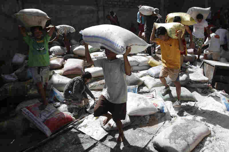 Survivors bring bags of rice from a warehouse which they stormed due to a shortage of food in Tacloban.