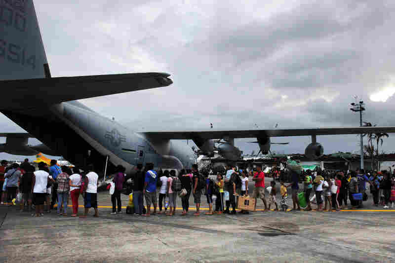 Typhoon survivors line up to board a U.S. military C-130 plane for Manila after the plane arrived carrying relief supplies in Tacloban.