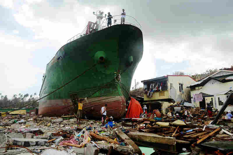 People walk among debris next to a ship washed ashore in Tacloban.