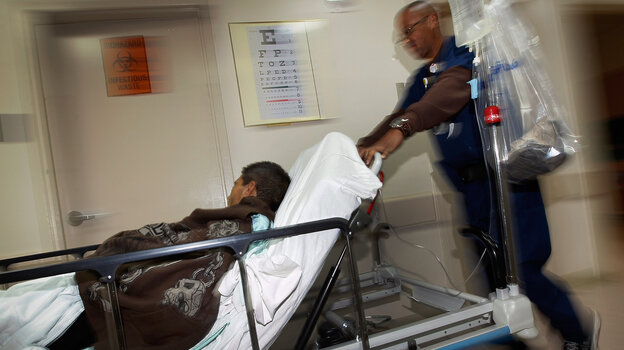 Wilfred Mobley pushes through the emergency room patient at the University of Miami Hospital in 2012.