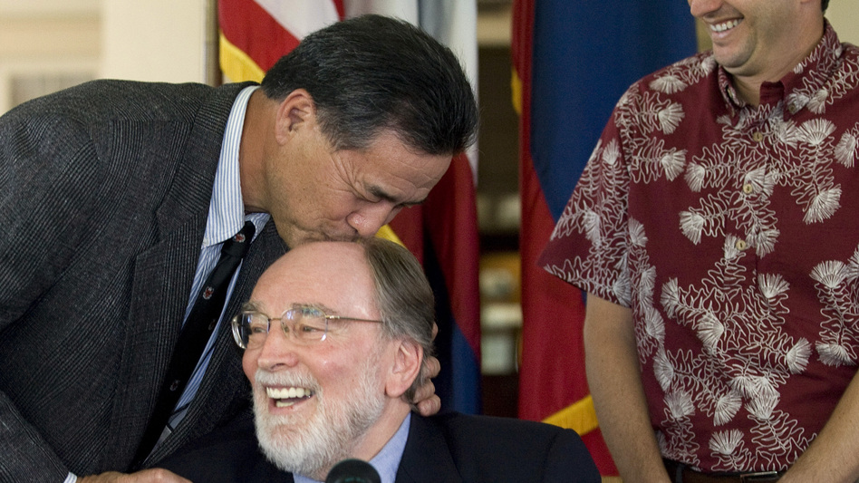 Hawaii state Sen. Clayton Hee playfully gives Gov. Neil Abercrombie a kiss on the head before he signs the Hawaii Civil Unions bill into law at a ceremony in February 2011 in Honolulu. (AP)