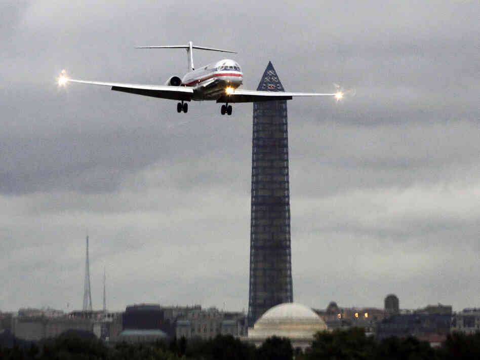 An American Airlines jet passes the Washington Monument as it lands at Ronald Reagan National Airport. That's one of seven airports where American and US Airways must now make room for low-cost competitors under a settlement with the Justice Department.
