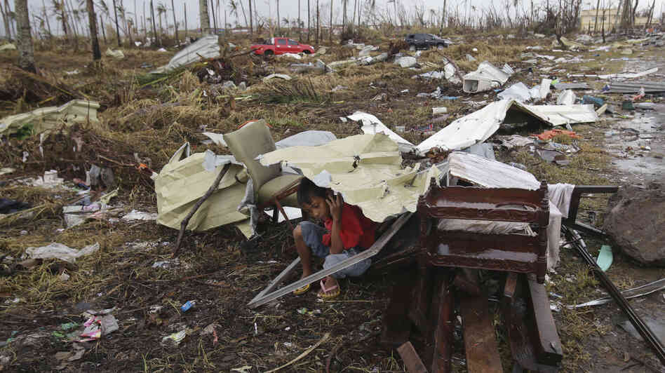 A young survivor uses the remains of a house to shield him from rain in Tacloban, Philippines, on Tuesday. Four days after Typhoon Haiyan struck the eastern Philippines, assistance is only just beginning to arrive. Authorities estimate the storm killed 10,000 or more.