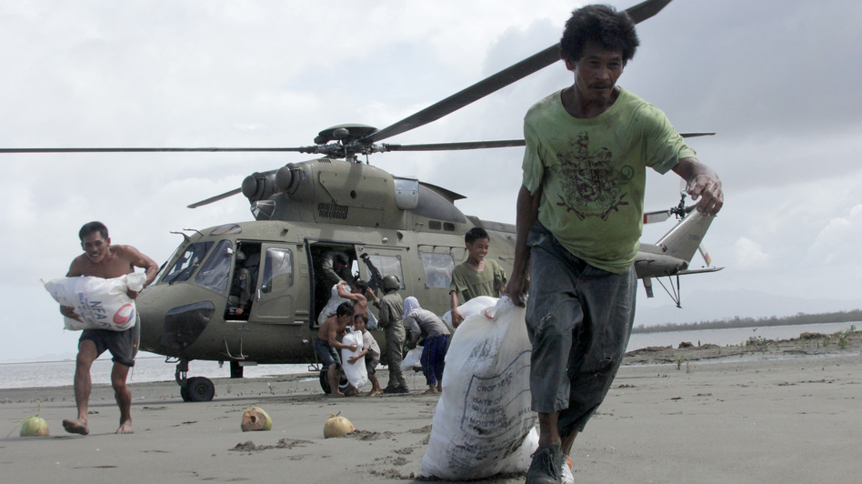 Survivors of Typhoon Haiyan in the central Philippines coastal village of Capiz got some help Monday when a Filipino military helicopter brought some much-needed food. (Tara Yap/AFP/Getty Images)
