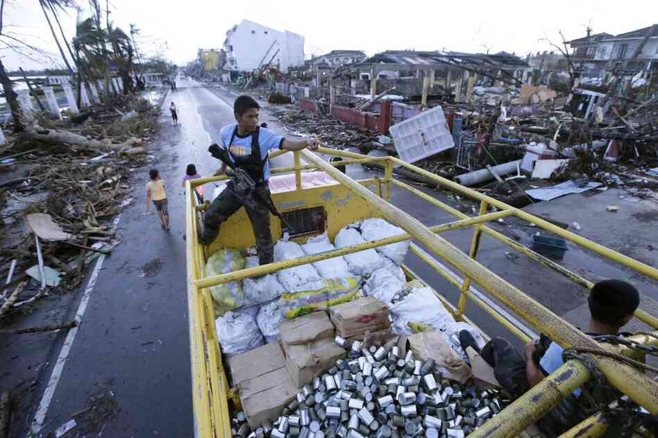 Filipino policemen secure a truck load of relief goods in the typhoon devastated city of Tacloban, on the eastern Filipino island of Leyte on Tuesday. Aid workers and relief supplies were being poured into eastern provinces hit by Typhoon Haiyan, which aid agencies and officials estimated has left thousands dead and staggering destruction in its wake.