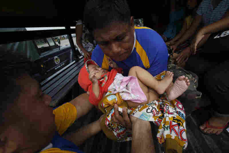 A child, one of the survivors who was evacuated from the disaster zone, is carried into a military truck with her family after they arrive via at Villamor Air Base in Manila. Rescue workers tried to reach towns and villages in the central Philippines on Tuesday that were cut off by the typhoon.