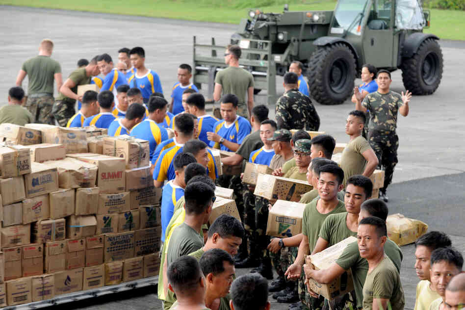 U.S. and Filipino military personnel prepare relief goods for transporting at the military base in Manila, before sending the packages to Tacloban which bore the brunt of the typhoon.