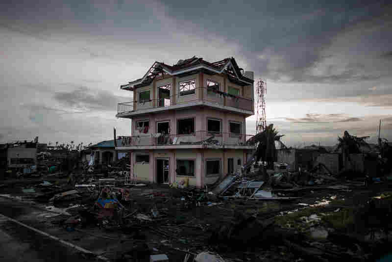 "The sun sets behind a house damaged by Typhoon Haiyan outside the airport in Tacloban. ""It looks like a 50-mile wide tornado"" flattened everything in and around the city of Tacloban, according to Marine Brig. Gen. Paul Kennedy."