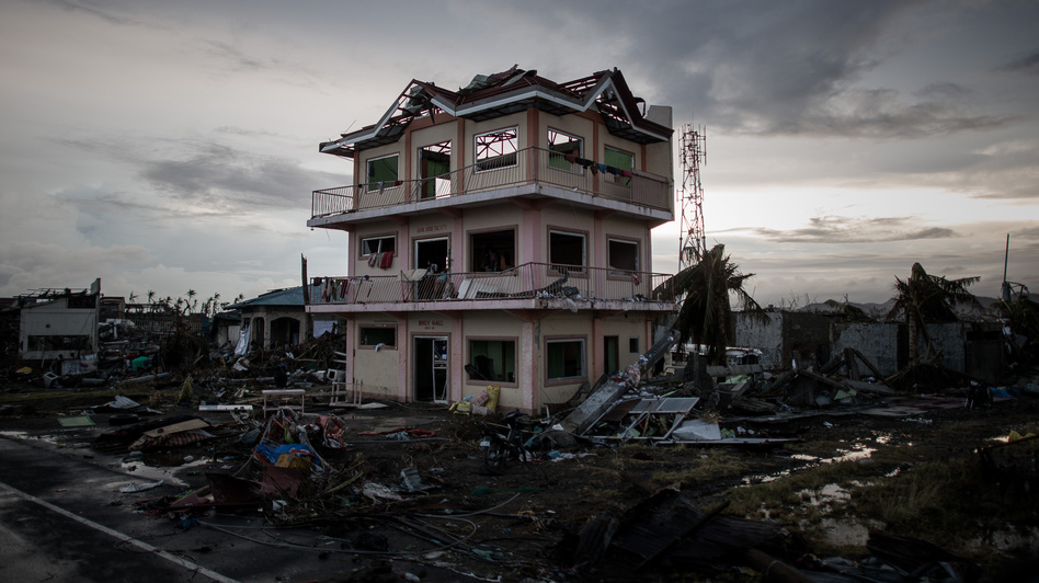 The sun sets behind a house damaged by Typhoon Haiyan outside the hard-hit city of Tacloban. The Philippines has gotten better at preparing for typhoons, but remains extremely vulnerable. (Philippe Lopez/AFP/Getty Images)