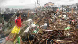On Tuesday, a boy sat in the debris of destroyed houses in Tacloban, on the eastern Filipino island of Leyte.