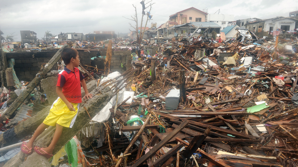 On Tuesday, a boy sat in the debris of destroyed houses in Tacloban, on the eastern Filipino island of Leyte. (Noel Celis /AFP/Getty Images)