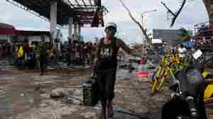 Residents collect gasoline at a damaged gas station in Tacloban, Philippines, on Wednesday.