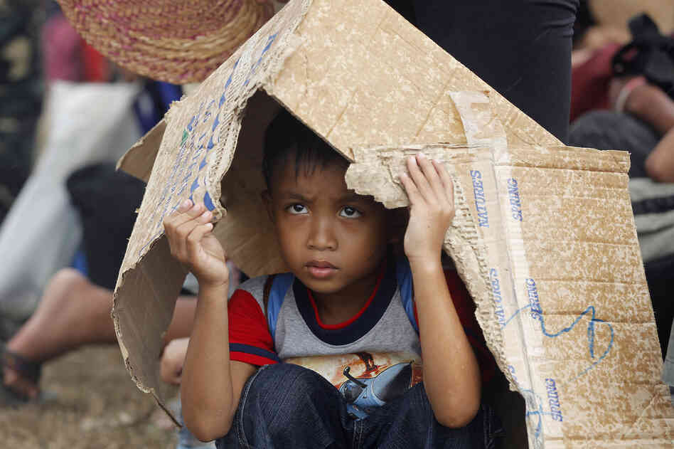 A young boy hides from the rain while waiting for an evacuation flight at the airport in Tacloban, central Philippines, on Thursday.