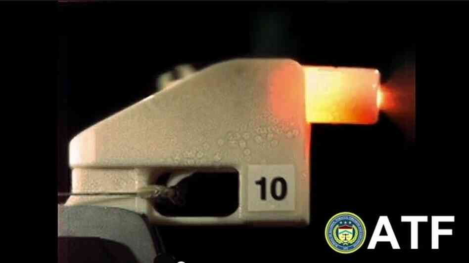 An all-plastic gun fires a bullet in this screenshot from a video made by the Bureau of Alcohol, Tobacco, Firearms and Explosives.