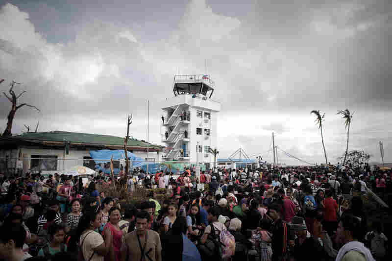 "Typhoon victims wait at an airport to leave Tacloban. A fight for ""sheer survival"" is underway as more than 220,000 people search for food, water and other essentials in Tacloban, NPR's Anthony Kuhn said Wednesday on Morning Edition."