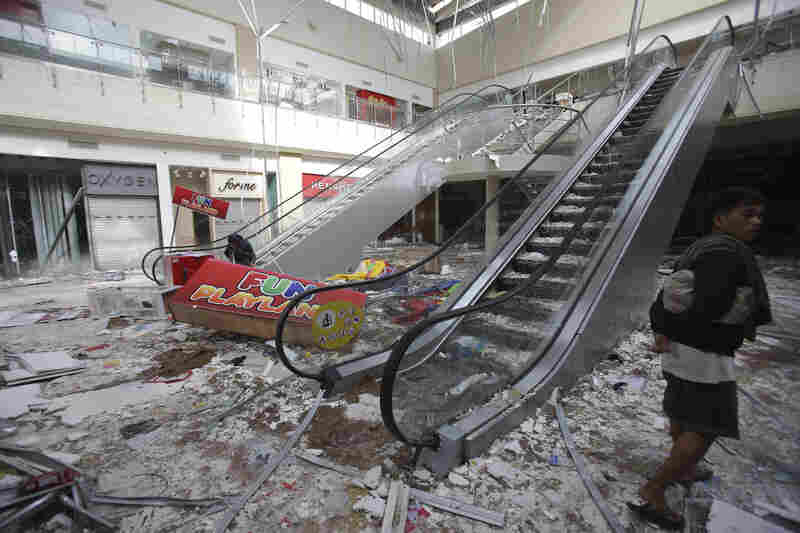 Tacloban residents walk through a mall that flooded and, some say, was looted.