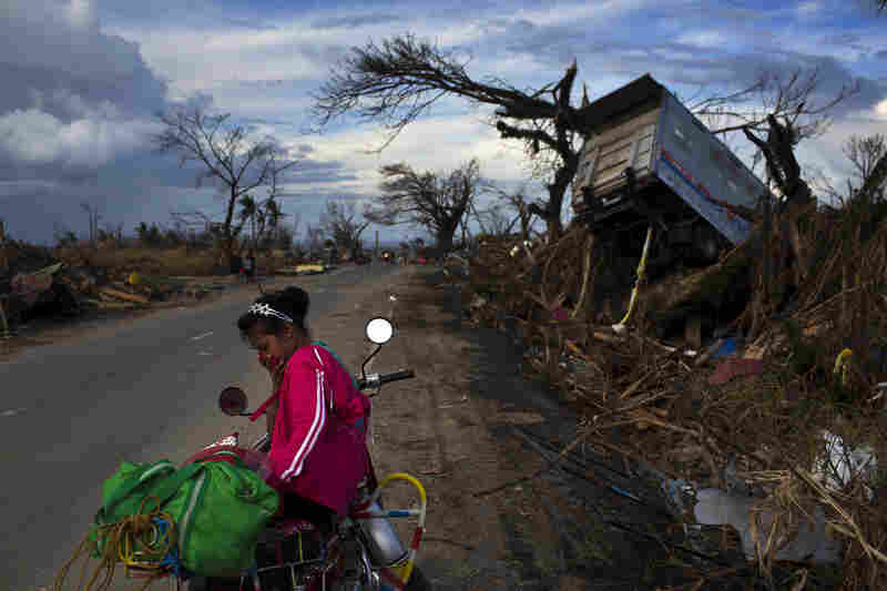 A woman rests at the side of a road with her family's belongings near the Typhoon Haiyan ravaged city of Tacloban, central Philippines on Wednesday. The storm slammed into the Philippines five days ago and left a trail of destruction in multiple provinces.