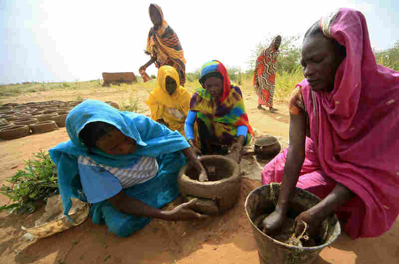 Women make fuel-efficient mud stoves in Darfur, Sudan, in October 2012. The stoves save women trips for firewood, a task that leaves them vulnerable to attack.