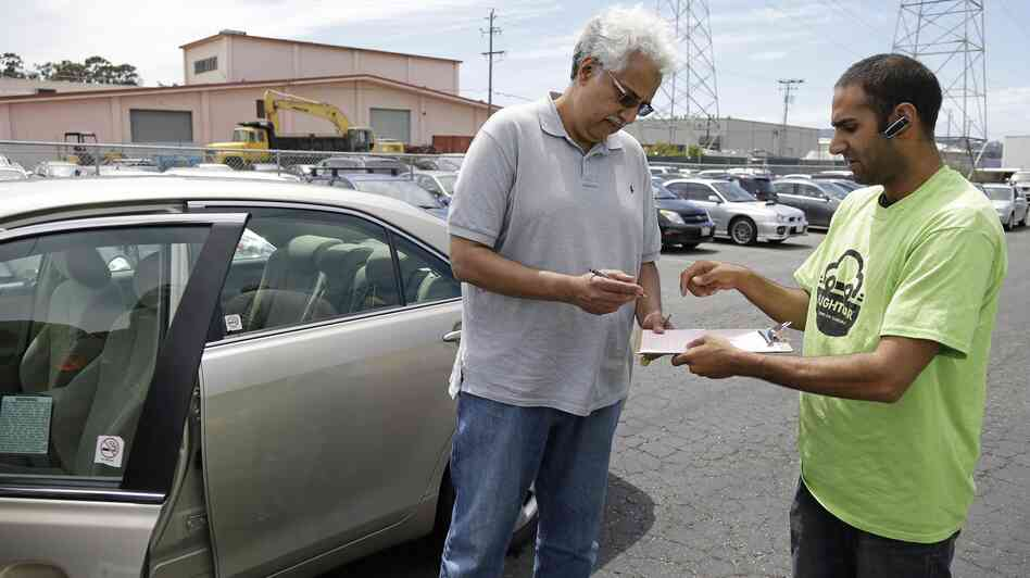 A man picks up a rental car in in Burlingame, Calif., near San Francisco International Airport this summer. The car was left with the FlightCar company by a traveler who then flew out of the