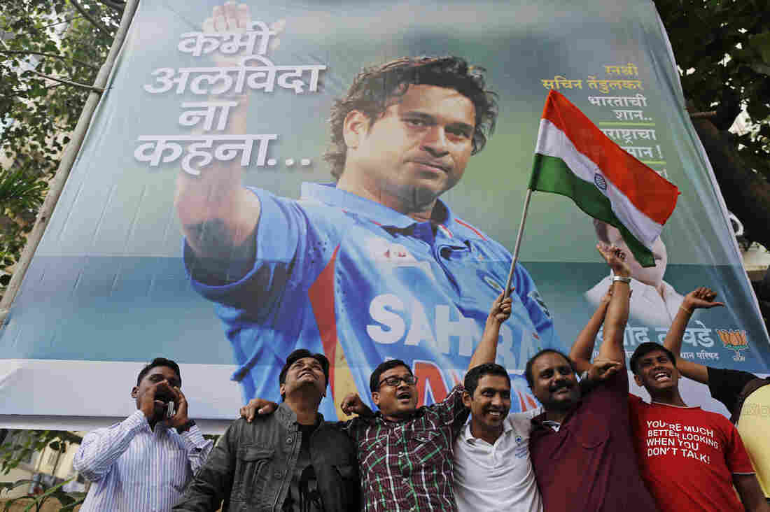 Cricket fans holding an Indian national flag cheer in front of a billboard of superstar cricketer Sachin Tendulkar outside a stadium in Mumbai on Thursday. India's favorite son dominated the sport for nearly a quarter of a century. Now, that fabled career is coming to a close.