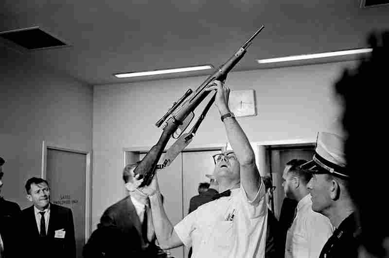 Police Lt. J.C. Day holds the bolt-action rifle with telescopic sight, allegedly used in the assassination.