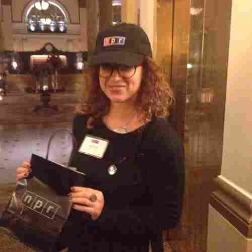 Erica Berger holding NPR swag and working her best Vanna White inspired pose.